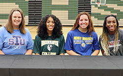 Four female student-athletes sit at a table prepared to sign letters of intent